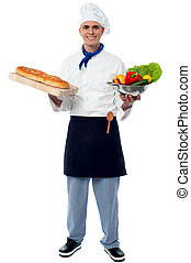 Chef holding fresh vegetables and bread
