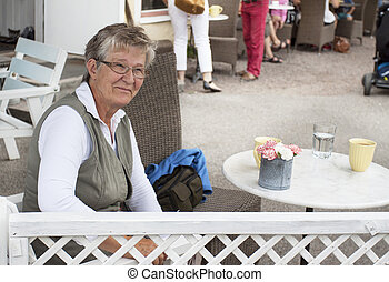 Old smiling woman in cafe
