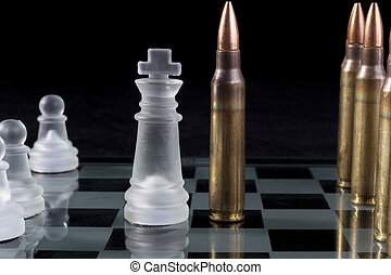 Strategy - Machine gun bullets on glass chess board on black...