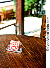 No smoking sign on wood table in cafe