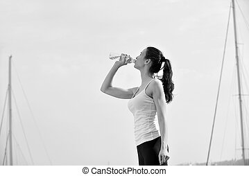 Young beautiful woman drinking water after fitness exercise...