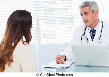 Serious doctor talking with his patient and writing on a...