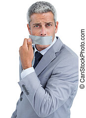 Businessman taking off duct tape on mouth on white...