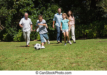 Happy multi generation family playing football together in...