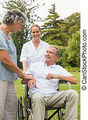 Happy man in a wheelchair talking with his nurse and wife