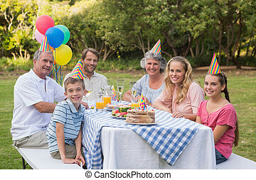 Family smiling at camera at birthday party outside at picnic...