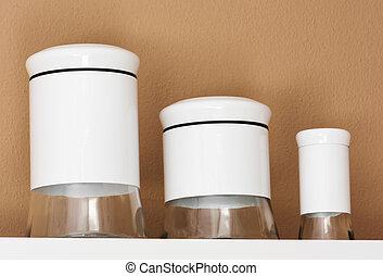 Empty white glass jars on a shelf