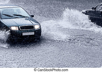 Driving in stormy weather - Cars driving through deep puddle