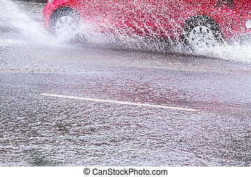 Red car splashes - Splash by a car as it goes through flood...