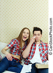 Funny or sad? - Portrait of young couple watching TV and...