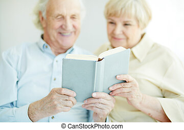 Reading together - Senior couple holding and reading book...