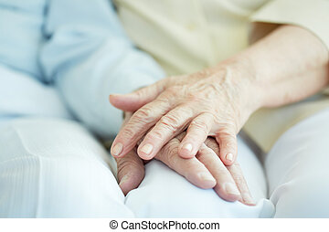 Union of seniors - Close-up of senior female hand on that of...