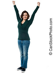 Jubilant woman with raised arms celebrating victory - Full...