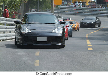 Sports-cars at a racetrack - Black German sports car on a...