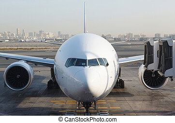 Front view of airplane at gate and gangways for the plane