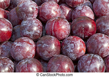 Fresh plums on a market as background, format filling
