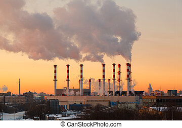 Smoking pipes of thermal power plant against sunrise