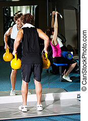Athletic people working out with equipments - Guy and girl...