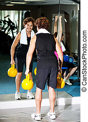 Fitness people in action, exercising - Mirror reflection of...