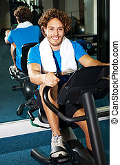 Handsome man at the gym doing static cycling