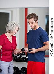 Trainer with a senior woman in the gym - Young handsome male...