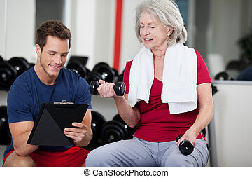 Trainer instructing a senior woman in the gym - Handsome...