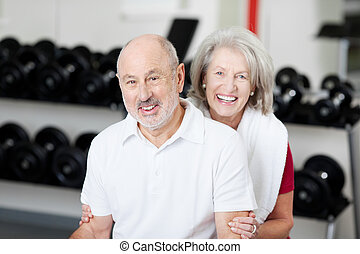 Smiling affectionate senior couple at the gym posing in...
