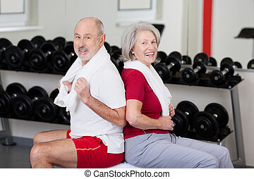 Senior couple exercising at a gym sitting back to back with...
