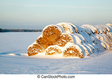 haystack under snow at sunset