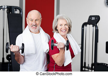 Senior couple working out with weights