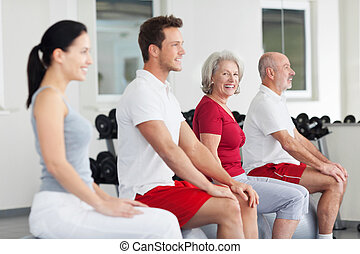 Senior woman training in a group at the gym turning to smile...