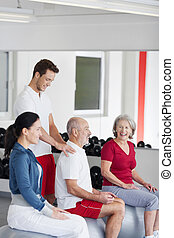 Trainer helping a senior man at the gym correcting his...