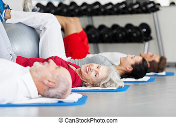 Elderly woman working out in a gym lying on a mat with a...