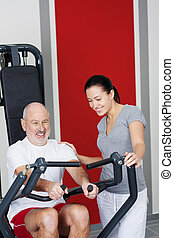 Personal fitness trainer with a senior man - Attractive...