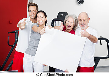 Family With Blank Billboard Gesturing Thumbs Up In Gym -...
