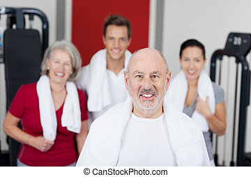 Senior Man Smiling With Family In Gym - Portrait of senior...