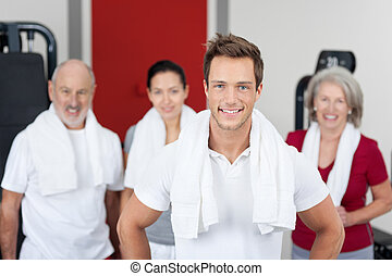 Young Man Smiling With Family In Gym - Portrait of young man...