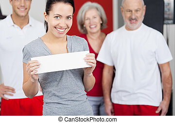 Woman Holding Blank Paper With Family In Background At Gym -...