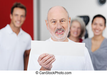 Man Displaying Blank Paper With Family At Gym - Portrait of...