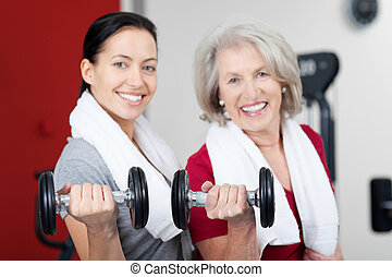 Mother And Daughter Lifting Dumbbells In Gym - Portrait of...