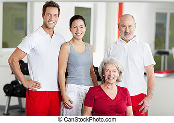 Family Smiling Together In Gym - Portrait of family of four...