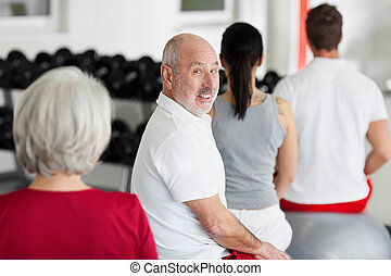 Family Sitting On Swiss Balls In Gym - Portrait of senior...