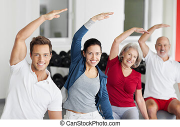 Family Doing Stretching Exercise In Gym - Portrait of happy...