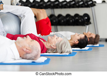 Family Exercising While Lying On Mat At Gym - Side view of...