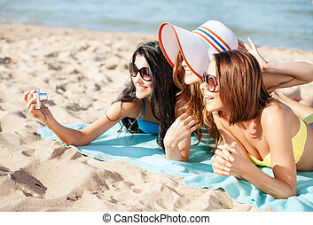 girls making self portrait on the beach - summer holidays,...