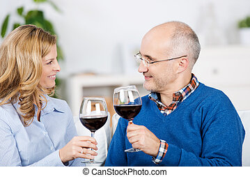 Couple Toasting Red Wineglasses While Looking At Each Other...