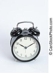 Vintage black color alarm clock on the write background