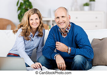Couple with a laptop and paperwork at home