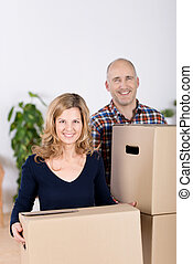 Couple Carrying Cardboard Boxes At New Home - Portrait of...