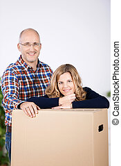 Couple taking a break from packing up the house leaning on...